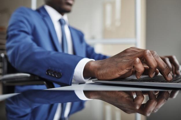 Close-up van afrikaanse zakenman typen op toetsenbord op laptop aan de tafel