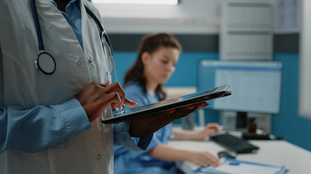 Close up van afro-amerikaanse arts met behulp van tablet met touchscreen
