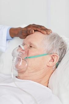 Close up van afro-amerikaanse arts troostende senior patiënt liggend in ziekenhuisbed met zuurstofmasker