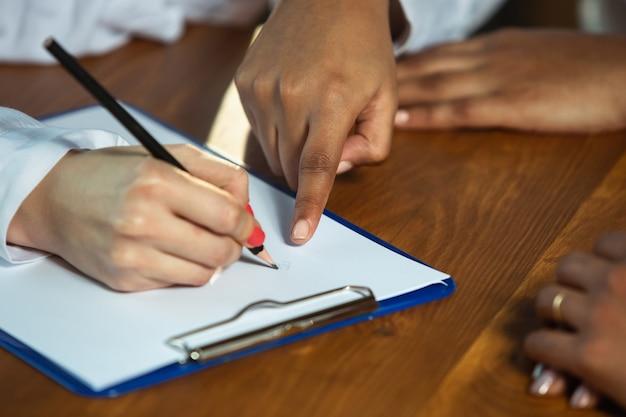 Close-up van afro-amerikaanse en blanke mensenhanden die op houten tafel schrijven. vrouwelijke handen met de potloden die iets opmerken. business, teamwork, studeren, onderwijs, financiën concept.