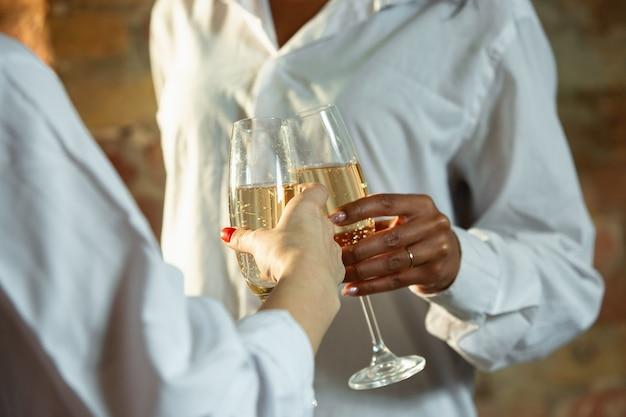 Close up van afro-amerikaanse en blanke mensenhanden. houd een bril met champagne vast, vier feest. zaken, teamwork, studeren, onderwijs, advertentie, financiën, liefde en relatie, familieconcept.
