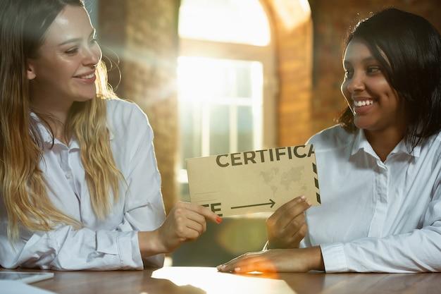Close-up van afro-amerikaanse en blanke mensenhanden met certificaat of uitnodigende kaart. gelukkige, lachende en schattige vrouwen. zaken, teamwork, studeren, onderwijs, financiën, feestelijk concept.