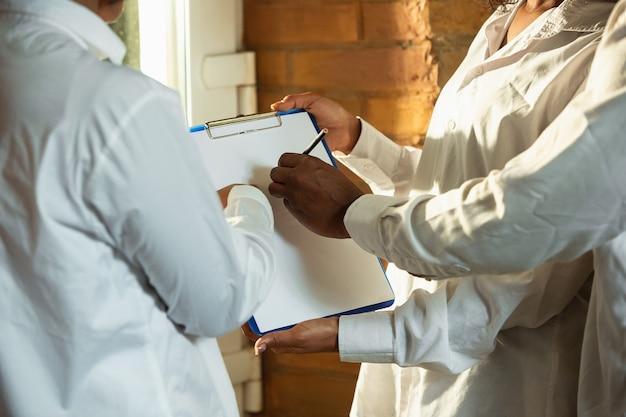 Close up van afro-amerikaanse en blanke mensenhanden. witte lakens vasthouden en aanwijzen. zaken, teamwork, studeren, onderwijs, advertentie, financiën, liefde en relatie, familieconcept. kopieerruimte.