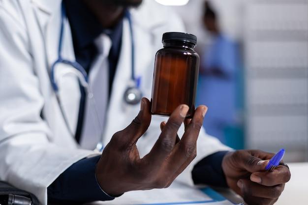 Close up van afro-amerikaanse hand met fles pillen