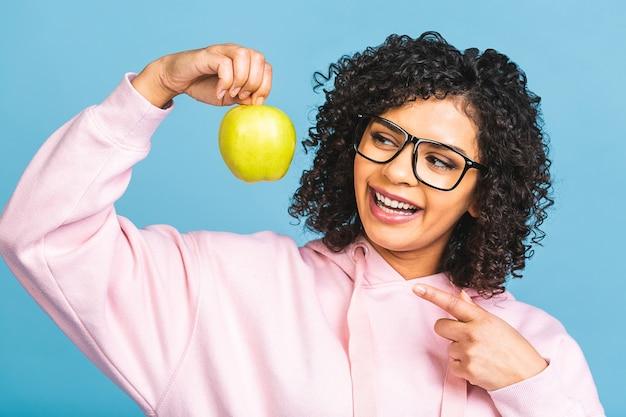 Close-up van afro-amerikaanse jonge vrouw die gezonde brede glimlach aantoont, groene appel, tevreden klant klant aanbeveelt tandheelkundige whitening service, mondhygiëne en behandeling