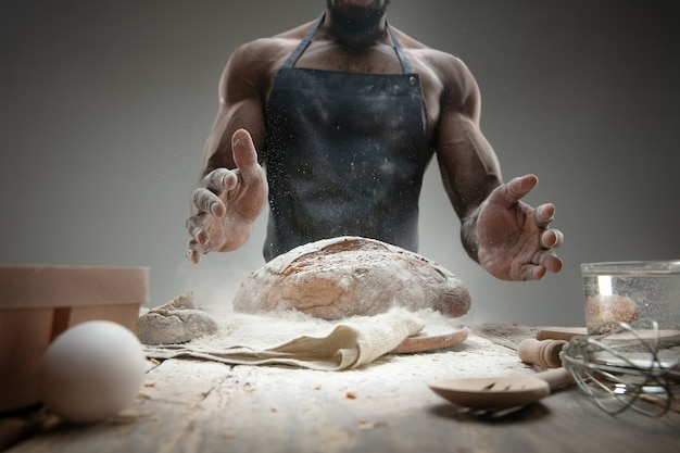 Close up van afro-amerikaanse man kookt vers ontbijtgranen, brood, zemelen op houten tafel. lekker eten, voeding, ambachtelijk product