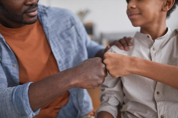 Close-up van afro-amerikaanse vader en zoon die met de vuist stoten na het winnen van het spel om succes te vieren, kopieer ruimte