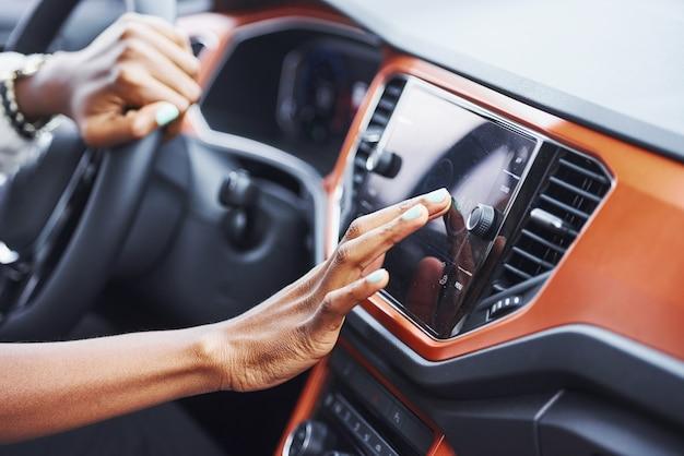 Close-up van afro-amerikaanse vrouw handen binnenkant van nieuwe moderne auto.