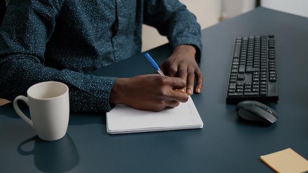 Close up van afro-amerikaanse zwarte persoon die aantekeningen maakt op kladblok met behulp van een pen mannelijke volwassen handen van re...