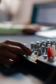 Close-up van afro-vlogger die geluidsaanpassingen maakt. sprekend tijdens livestreaming, blogger discussiërend in podcast met koptelefoon op.
