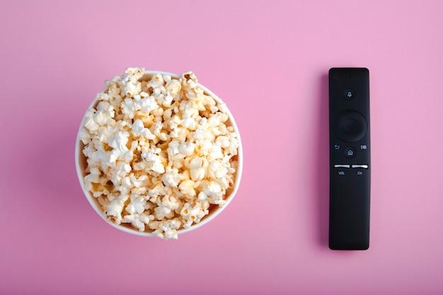 Close-up van afstandsbediening en papieren kopje popcorn