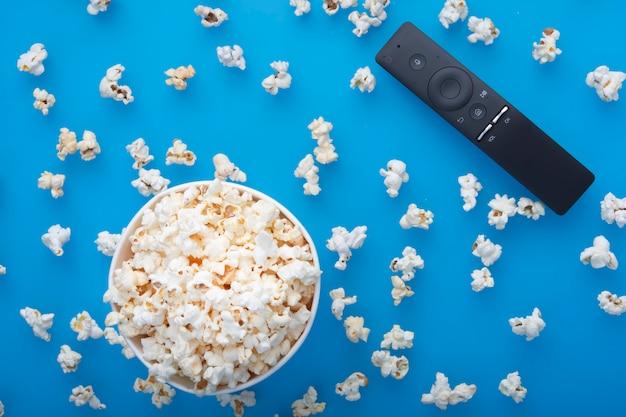Close-up van afstandsbediening en testy warme gemorste popcorn van boven gezien op blauw