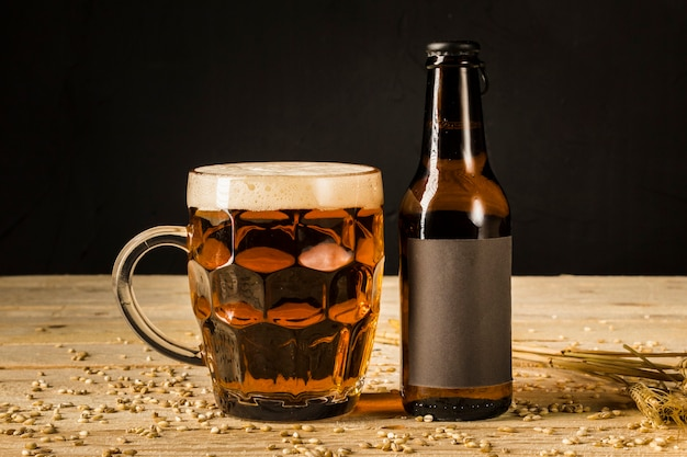 Close-up van alcoholisch glas en fles met oren van tarwe op houten oppervlak