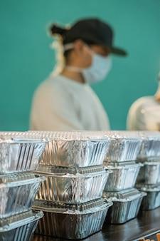 Close-up van aluminium dienbladen met te leveren voedsel. man met mondkap