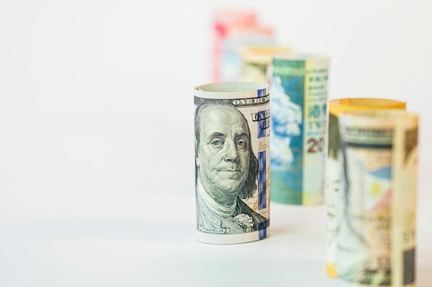 Close-up van amerikaanse dollarbankbiljet onder internationaal bankbiljet op wit. usd-bankbiljet is de belangrijkste en meest populaire valuta in de wereld.
