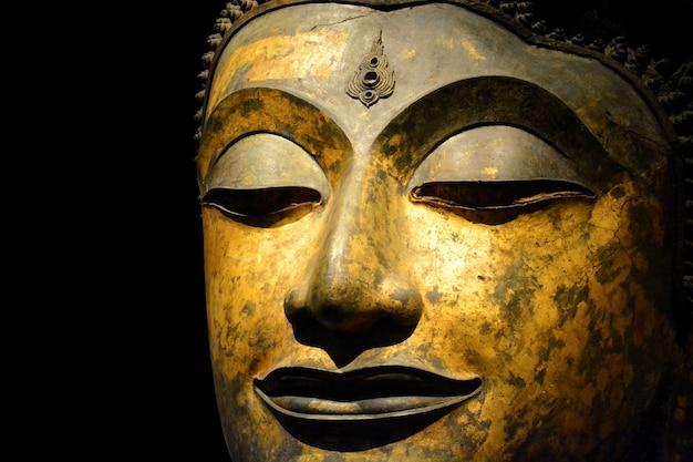 Close-up van antiek bronzen boeddha-gezicht geïsoleerd op zwarte achtergrond
