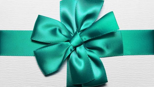 Close-up van aqua menthe inpaklint in vorm van boog voor witte geschenkdoos