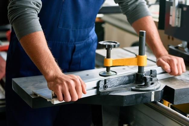 Close-up van arbeider die bank om metaal te snijden gebruiken
