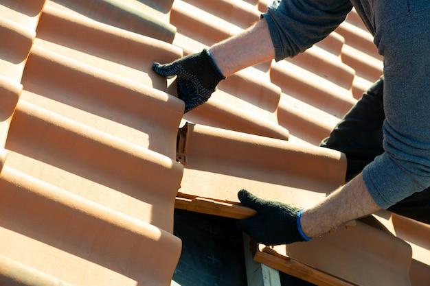 Close-up van arbeidershanden die gele ceramische dakpannen installeren die op houten planken worden gemonteerd die woningbouwdak in aanbouw behandelen.