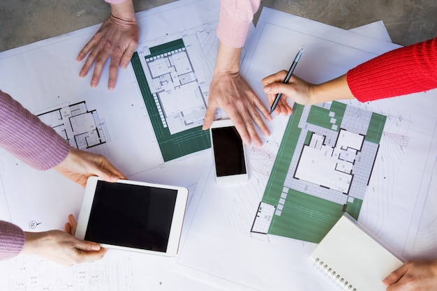 Close-up van architecten die met tekeningen werken en gadgets gebruiken