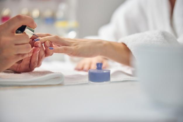 Close-up van artiest die vrouwelijke vingers bedekt met blauwe gellak aan tafel in kantoor