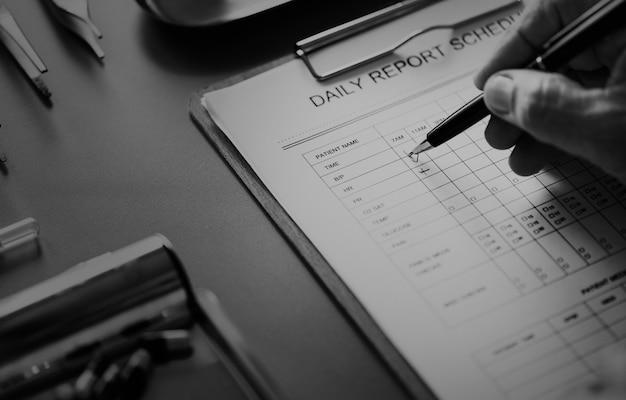 Close-up van arts die geduldige dagelijkse rapportcontrolelijst controleren