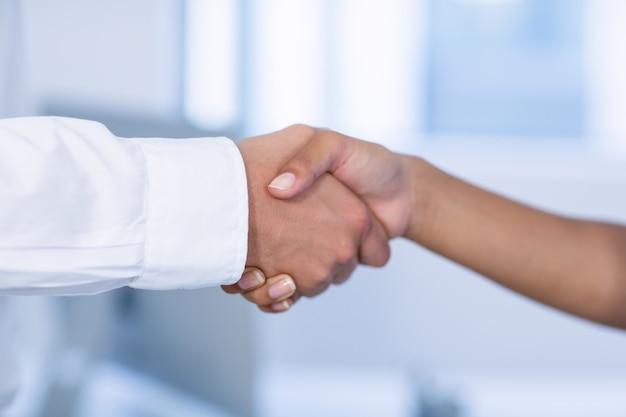 Close-up van arts en patiënt handen schudden