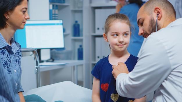Close up van arts met behulp van stethoscoop voor het luisteren van de hartslag van het kind. gezondheidszorgbeoefenaar arts-specialist in de geneeskunde die gezondheidszorgdiensten verleent consultatiebehandeling in ziekenhuiskast