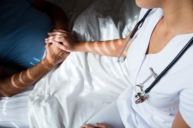 Close-up van artsen die hogere patiënt in slaapkamer troosten