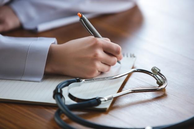 Close up van artsen handen met stethoscoop vellen en pillen op houten achtergrond