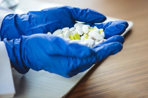 Close-up van artsenhanden die blauwe beschermende handschoenen dragen die een hoop pillen op houten tafel geven