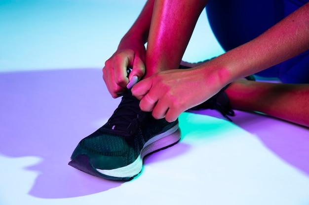 Close-up van atleet die haar schoenen bindt