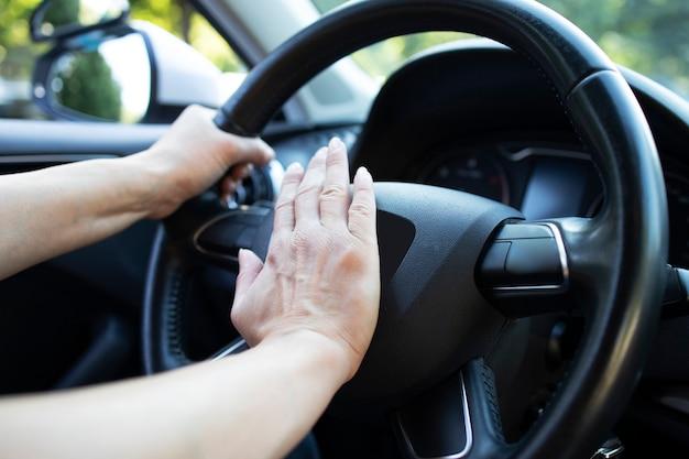 Close-up van auto stuurwiel en hand op hoorn of toeteren te drukken.
