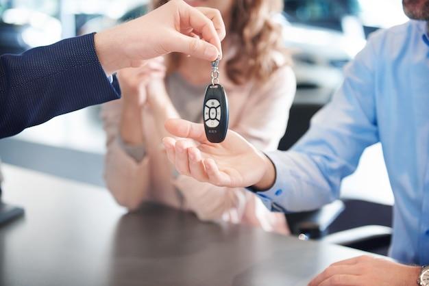 Close-up van autosleutels die aan de handen van klanten worden doorgegeven