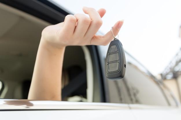 Close-up van autosleutels die aan vrouwelijke vinger hangen