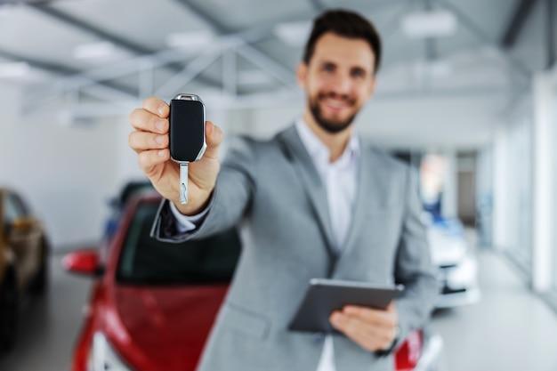 Close-up van autoverkoper die een sleutel houdt en richting camera inlevert terwijl hij in autosalon staat.