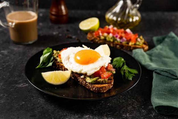 Close-up van avocadotoost met gebakken ei en tomaten