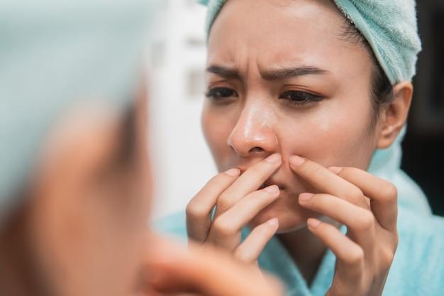 Close up van aziatisch meisje knijpen puistje op de wang naar de spiegel met handdoek op hoofd