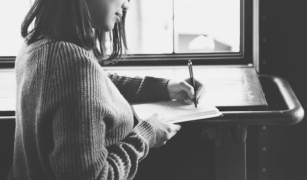 Close-up van aziatische vrouw die notitieboekje schrijft