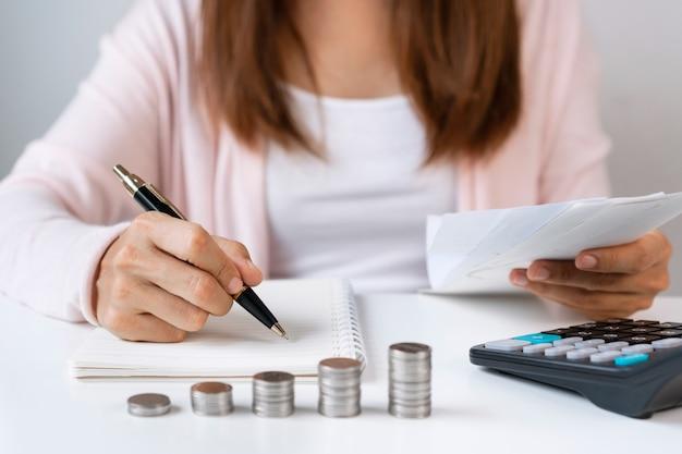 Close-up van aziatische vrouw maandelijkse kostenoverzicht op notebook schrijven terwijl ontvangstbewijs met rekenmachine
