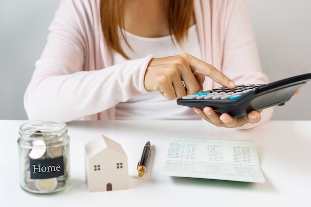 Close-up van aziatische vrouw met behulp van rekenmachine op witte tafel achtergrond. sparen, verzamel geld concept.