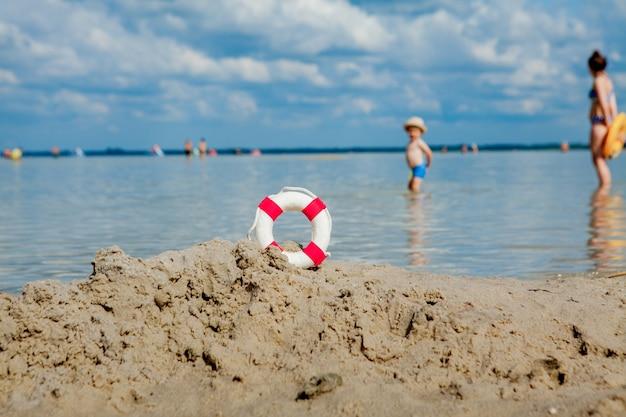Close-up van badmeester drijven op het strand en achtergrondzwemmers