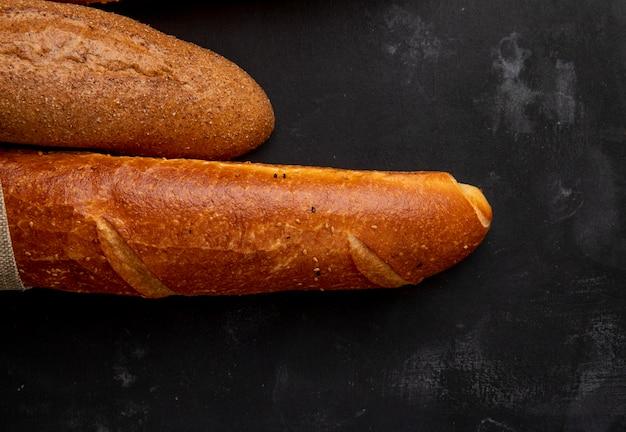 Close-up van baguettes aan de linkerkant en zwarte achtergrond met kopie ruimte