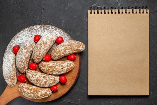 Close-up van banaan koekjes met fruit op bruin snijplank en notebook op donker