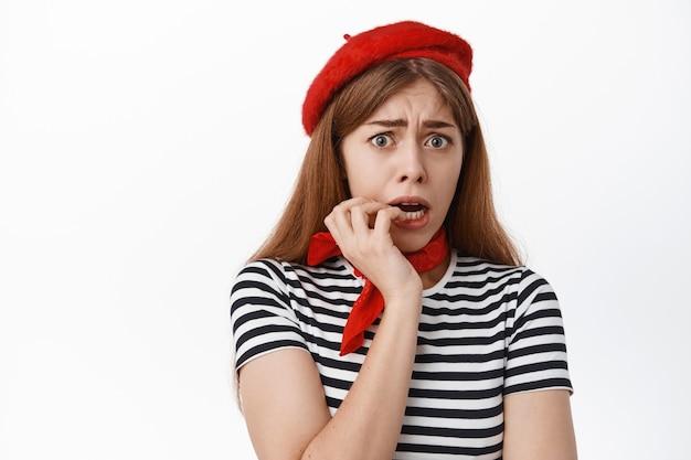 Close-up van bange jonge vrouw in baret, vingernagels bijtend en bang en angstig naar voren kijkend, bang voor iets, staande tegen een witte muur