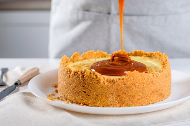 Close-up van banketbakker versieren oranje cheesecake met karamel in de keuken
