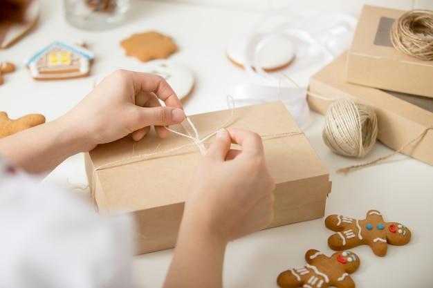 Close-up van banketbakkers handen inpakken een kartonnen doos