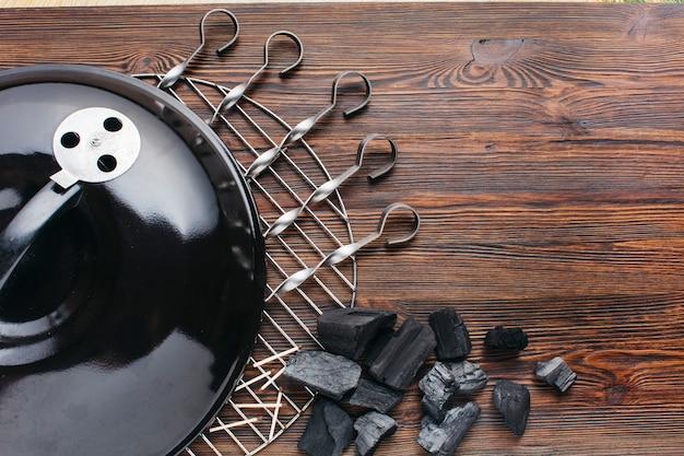 Close-up van barbecuetoestel met vleespen en steenkool