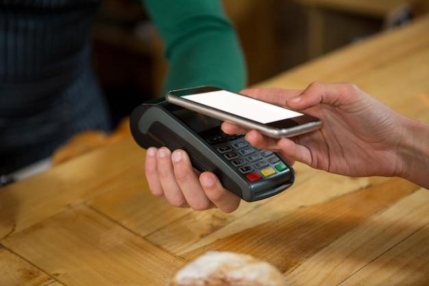 Close-up van barista die betaling via slimme telefoon accepteert