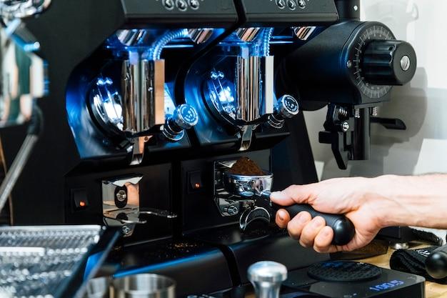 Close-up van barista portafilter vullen met verse gemalen koffie onder molen